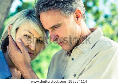 Closeup of loving man comforting woman in a park - stock photo