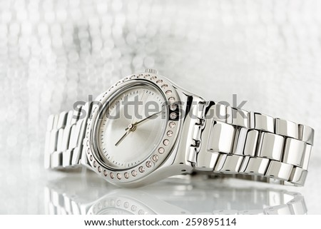 closeup of luxurious chrome watch against blurry background - stock photo
