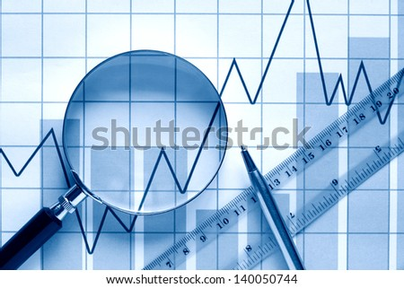 Closeup of magnifying glass near ruler and pen on paper background with business chart - stock photo