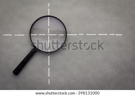 Closeup of magnifying glass on dark leather surface - stock photo