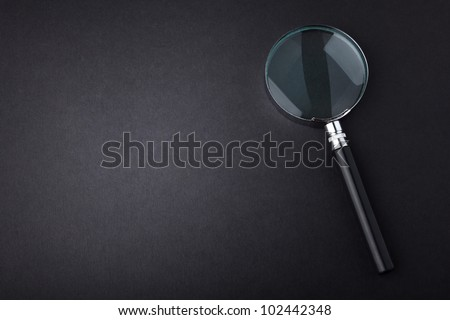 Closeup of magnifying glass on dark surface - stock photo