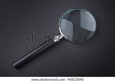 Closeup of magnifying glass on dark surface