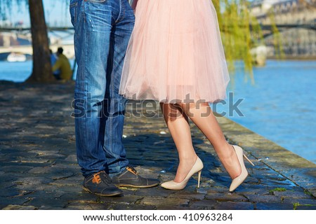 Closeup of male and female legs during a date. Romantic couple kissing on the Seine embankment in Paris