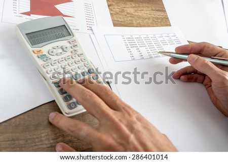 Closeup of male financial adviser calculating numbers on calculator as he prepares annual report and statistical analyse of income and expenses.  - stock photo