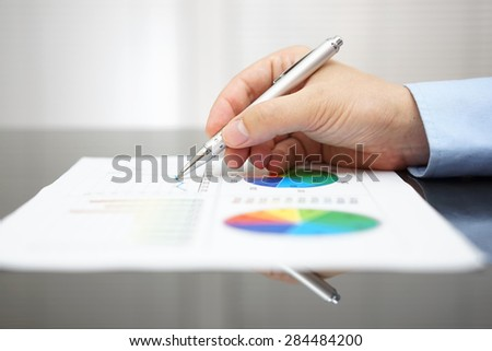 closeup of male hand analyzing business report on black desk - stock photo