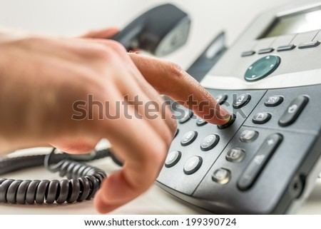 Closeup of male hand dialing a phone number making a business or personal phone call. - stock photo