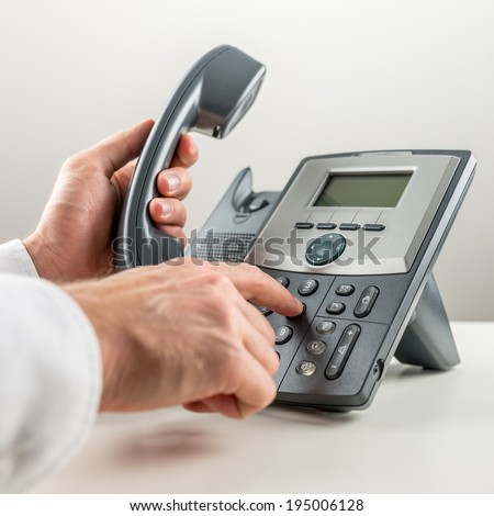 Closeup of male hand dialing telephone number and picking up a handset. Communication concept. - stock photo