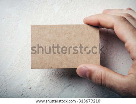 Closeup of male hand holding craft business card on concrete wal - stock photo