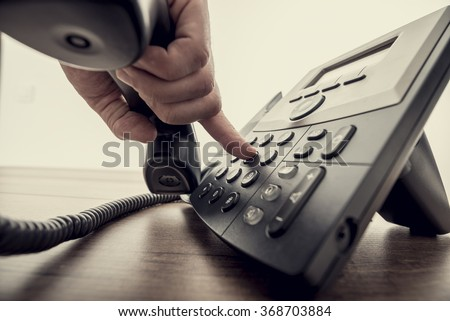 Closeup of male hand holding telephone receiver and dialing a phone number on a classical black landline telephone. Retro filter effect. - stock photo