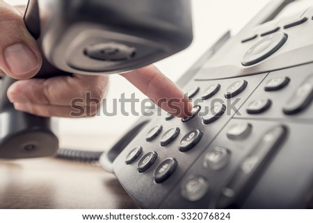 Closeup of male hand holding telephone receiver while dialing a telephone number to make a call using a black landline phone. With retro filter effect. - stock photo