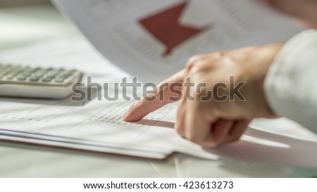 Closeup of male hand pointing to figures written on a document or report in form of statistical data. Conceptual of economy, finance and accounting.