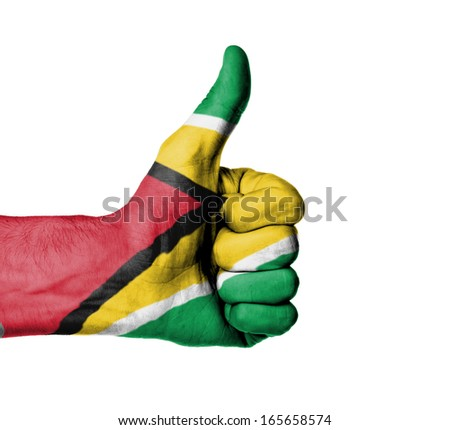 Closeup of male hand showing thumbs up sign, flag of Guyana - stock photo