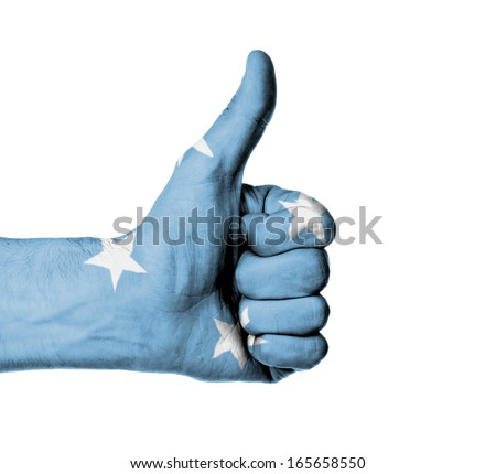 Closeup of male hand showing thumbs up sign, flag of Micronesia - stock photo