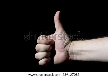 Closeup of male hand showing thumbs up sign on black background