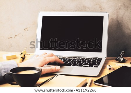 Closeup of male hand typing on blank laptop keyboard on wooden desk with coffee and office tools. Mock up - stock photo