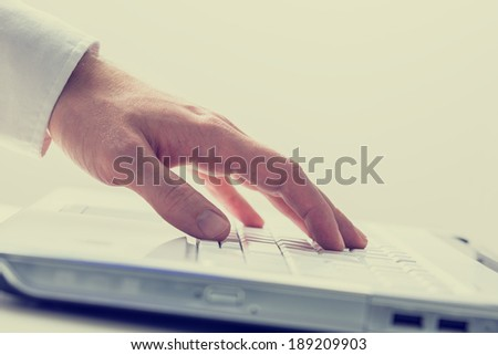 Closeup of male hand using white laptop computer. Conceptual of online business or e-learning, toned retro or instagram effect.
