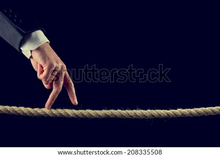 Closeup of male hand walking his fingers across a frayed rope, toned retro effect. - stock photo