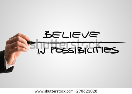 Closeup of male hand writing an inspirational message Believe in possibilities from behind a grey virtual screen, motivating you to never lose hope and ambition. - stock photo