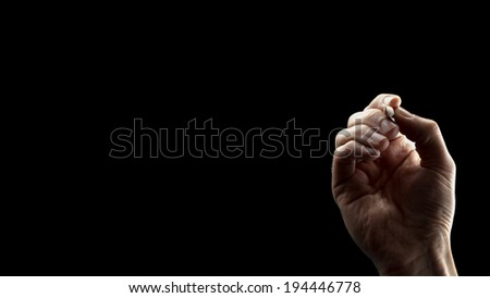 Closeup of male hand writing on blank virtual space over black background. - stock photo