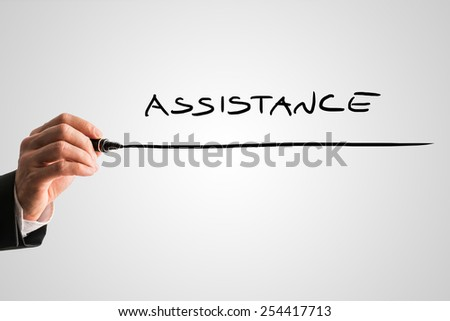 Closeup of male hand writing word Assistance on grey virtual screen. Conceptual of business support, customer care or medical aid and home assistance.