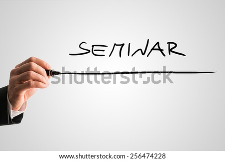 Closeup of male hand writing word Seminar on virtual screen. Conceptual of online seminar, e-business and e-learning.