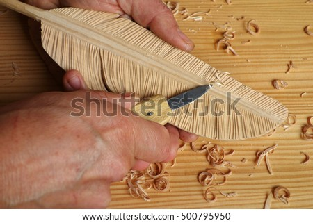 closeup of male hands holding a knife to carve a feather in wood