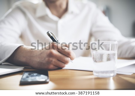 Closeup of male hands signing contract while working at his office, businessman working on documents - stock photo
