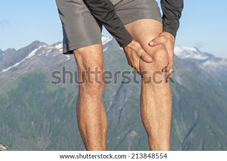 Closeup of male runner holding injured knee as he stands on scenic mountain top with snow capped peaks - stock photo