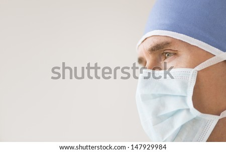 Closeup of male surgeon wearing surgical mask and cap looking away against gray background - stock photo