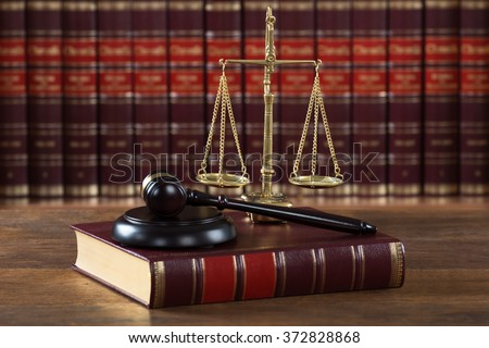 Closeup of mallet and legal book with justice scale on table in courtroom - stock photo