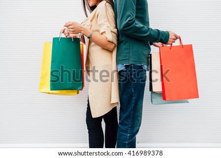 Closeup of man and woman holding their shopping bags - stock photo