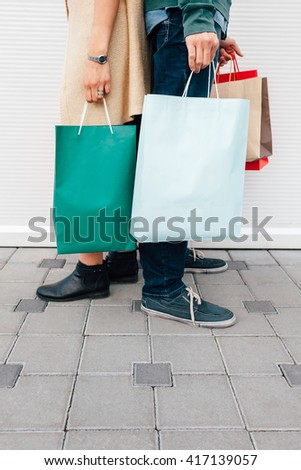 Closeup of man and woman holding their shopping bags with copy space