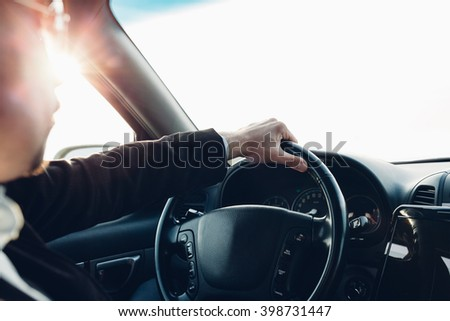 Closeup of man driving car at sunset with copy space
