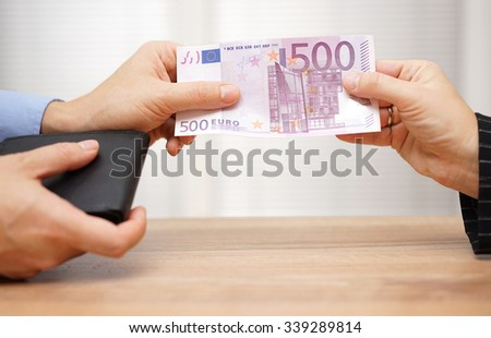 Closeup of man giving woman money from wallet - stock photo