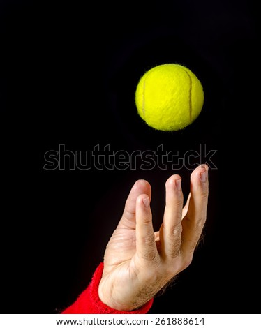 Closeup of man hand, arm, tossing the tennis ball, performing the serve. Tennis serve. Player on  competition. Isolated on black. Ball captured in the air. Left hand. - stock photo