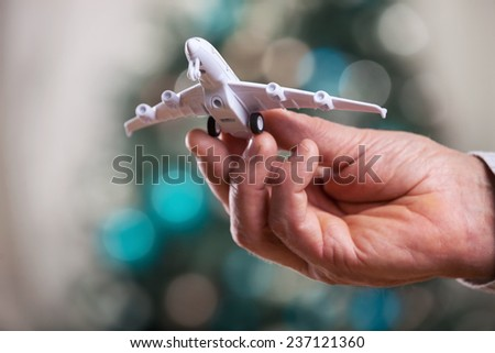 Closeup of man hand holding model of airplane  - stock photo