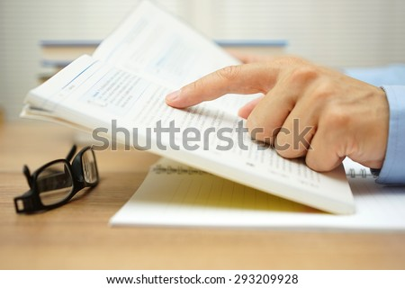 closeup of man hand reading a book