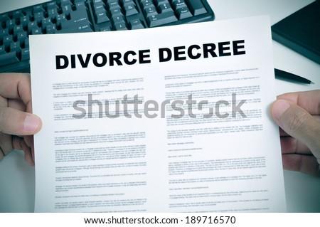 closeup of man hands holding a divorce decree on a desk - stock photo