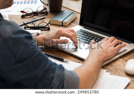 Closeup of man hands working on laptop in office  - stock photo