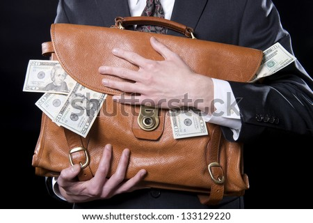 Closeup of man holding briefcase with money spilling out close to his chest - stock photo