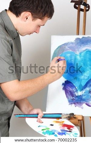 closeup of man holding brushes and palette, painting blue abstract picture - stock photo