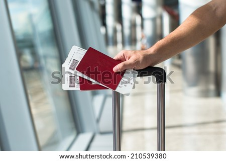 Closeup of man holding passports and boarding pass at airport - stock photo