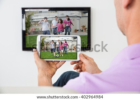 Closeup Of Man Holding Smartphone Connected To A TV - stock photo