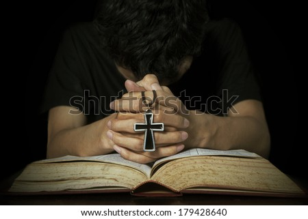 Closeup of man praying on bible while holding a cross - stock photo