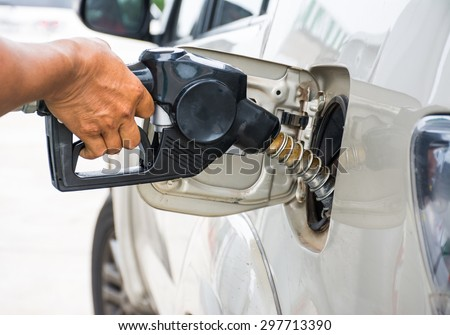 Closeup of man pumping gasoline fuel in car at gas station - stock photo