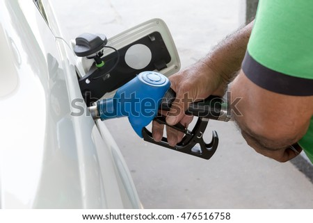 Closeup of man pumping gasoline fuel in white car at gas station. Pumping gas at gas station.