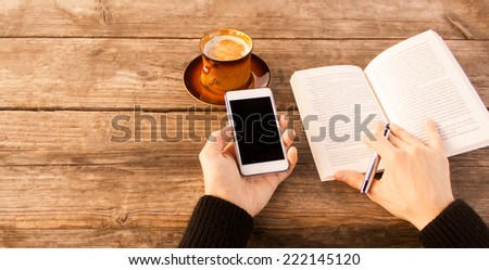 Closeup of man reading a book and using mobile smart phone with coffee outdoor. - stock photo
