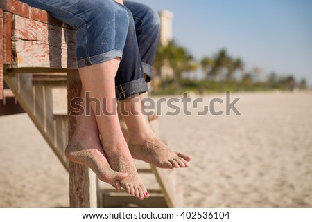 Closeup of man's and woman's feet. People sitting on the wooden deck on the beach. Couple enjoying summer day at the beach. Vacation mood.  - stock photo