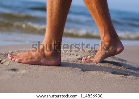 Closeup of man's feet at the shore