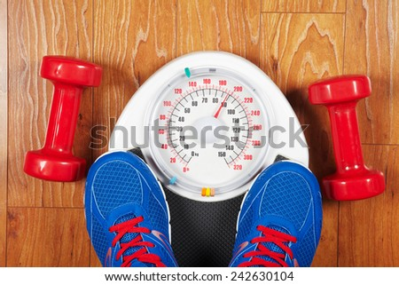 Closeup of man's feet on weight scale indicating overweight  - stock photo